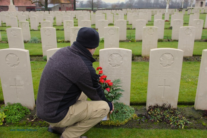 Man crouches down at commonwealth war grave in belgium