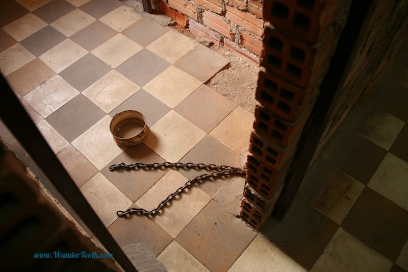 A cell with a old ammunition box for a toilet and the chains that bound the occupant by the ankle.