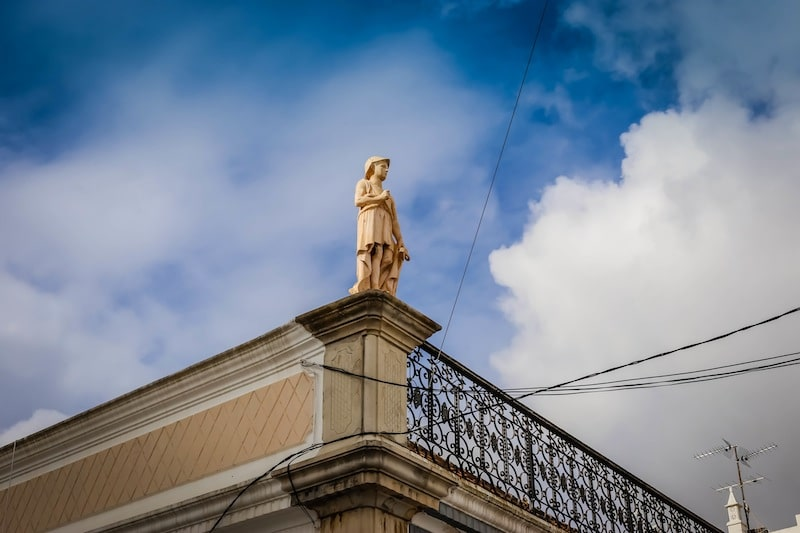 Statue of a boy atop a roof portugal