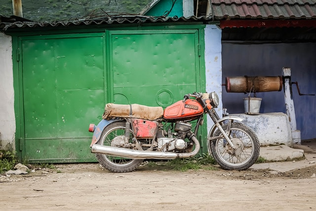 A motorbike parked beside one of the many community wells in Orhei village, Moldova