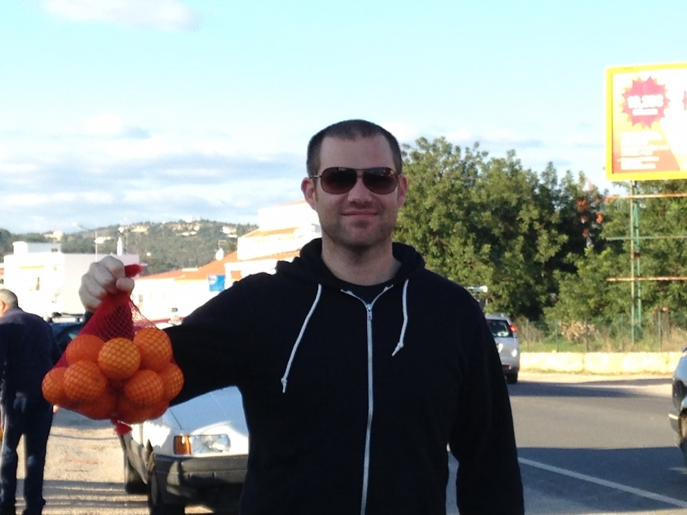 Geoff, picking up some juicing oranges during our housesit in Portugal