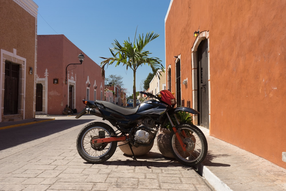a motorcycle and palm tree and colorful buildings