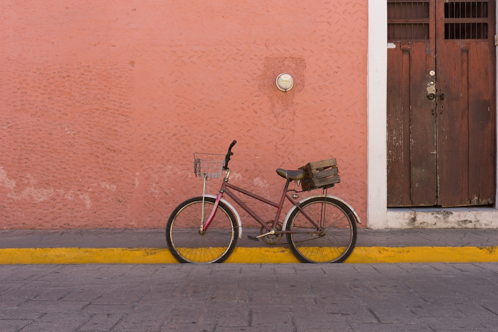 A bicycle with a basket against a colorful building Valladolid Mexico