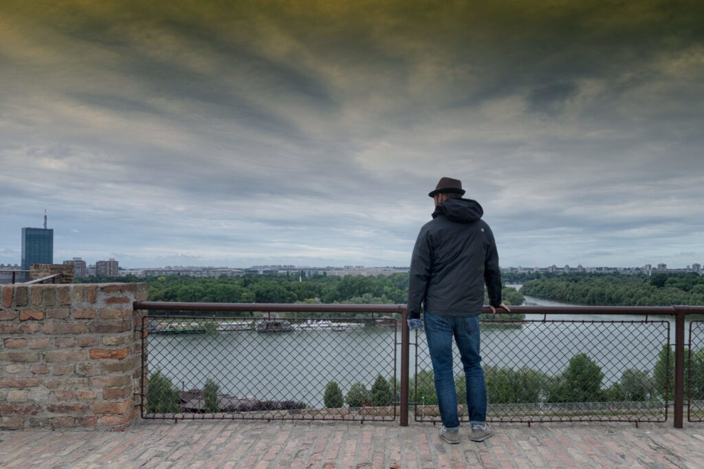 A man stands at Belgrade fort and looks at the city below