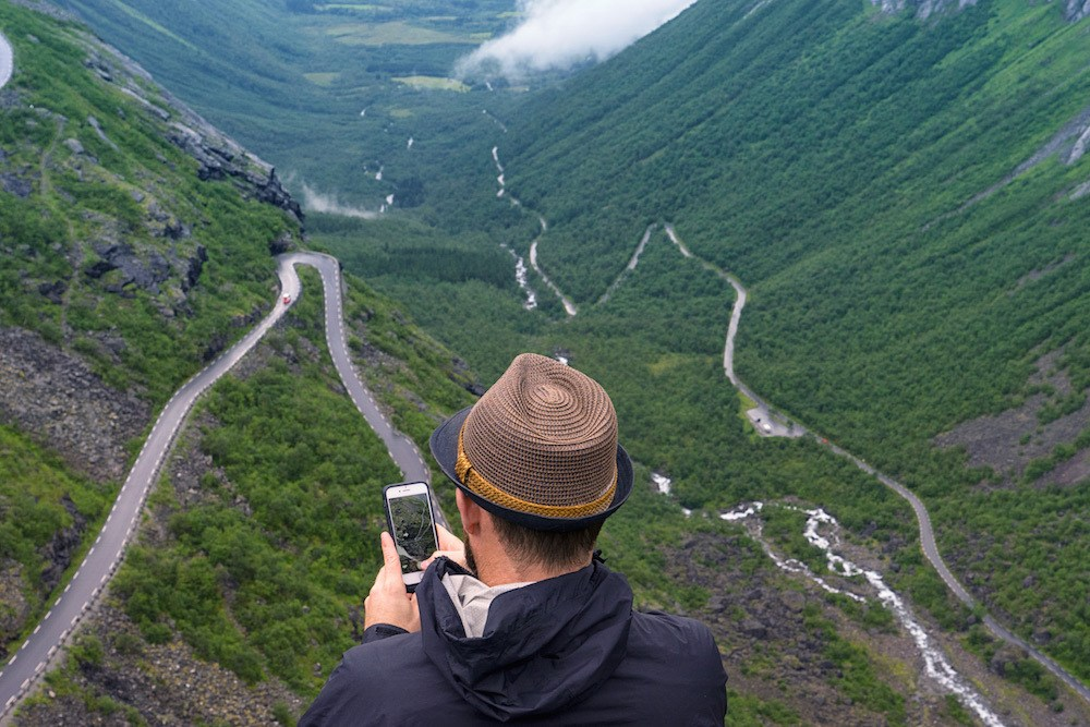 A Man Holds His Phone Above the Trollstigen in Norway