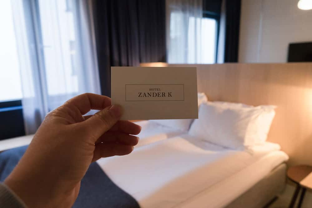 Hand holding Zander K business card in a hotel room