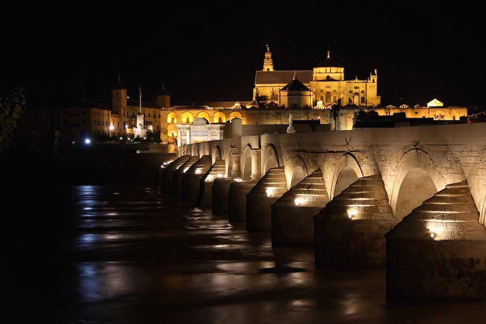 mezquita cordoba spain at night with bridge