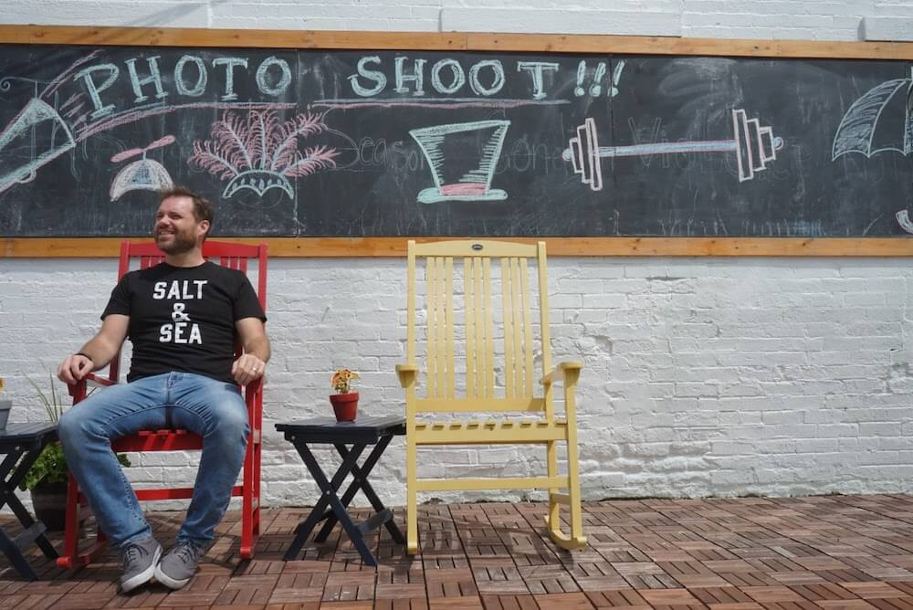 A man sits on a red chair against a chaolboard backgoround that says Photo Shoot