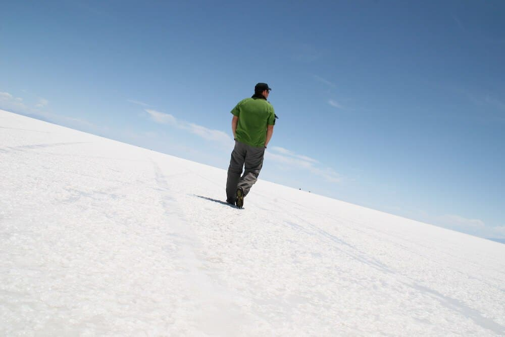A man walking away from the camera on the Bolivian salt flats on a clear day