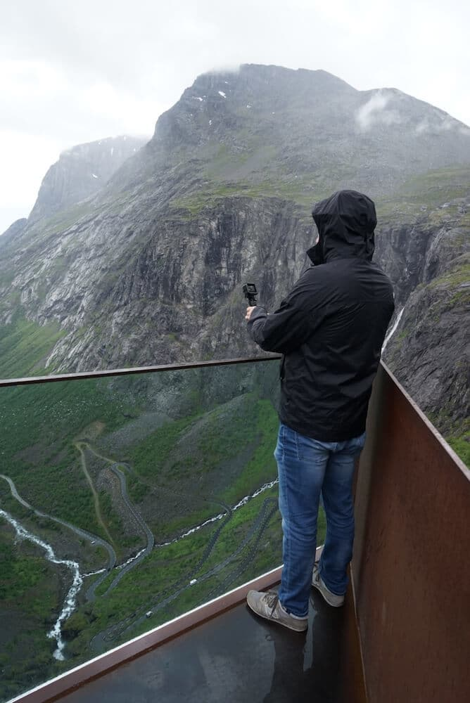 The back of a man holding a go pro overlooking the trollstigen on a viewing platform in Norway. The man is wearing a black rain jacket and jeans.