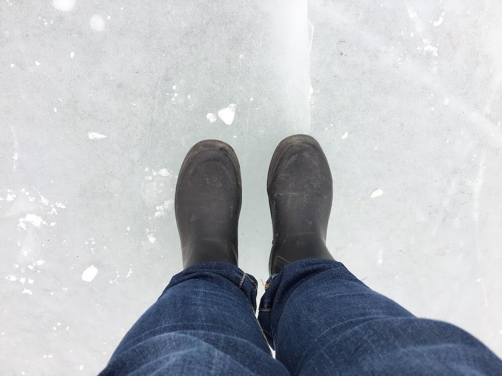 A pair of woman's legs and feet in jeans and black rubber rain boots standing on a frozen lake