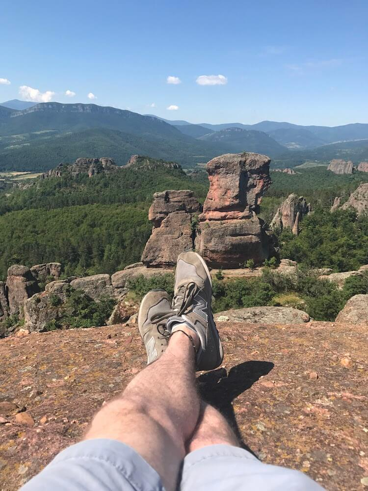 A man's legs wearing grey New Balance shoes can be seen at the top of Belogradchik Fortress in Bulgaria. Interesting rock formations are in the background.