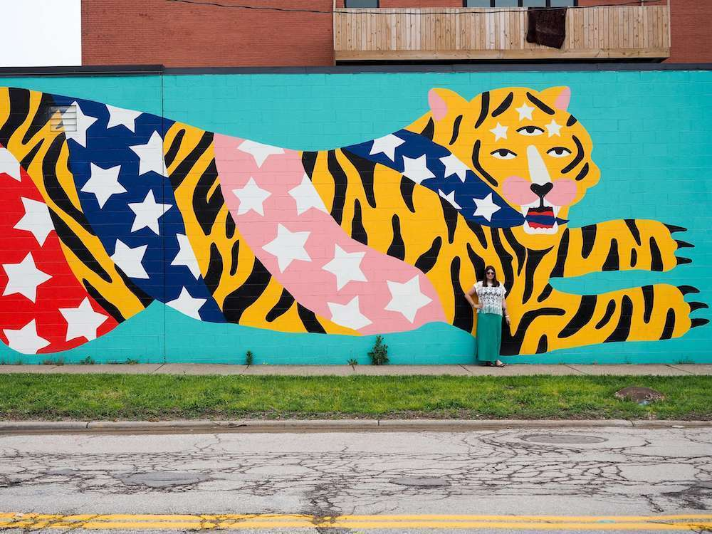 A woman stands in front of a tiger street art mural in Cleveland Ohio