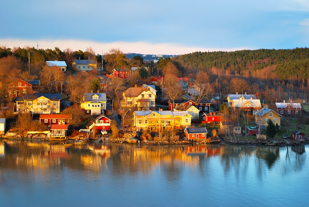 Beautiful wooden colorful houses near water in Finland at sunset