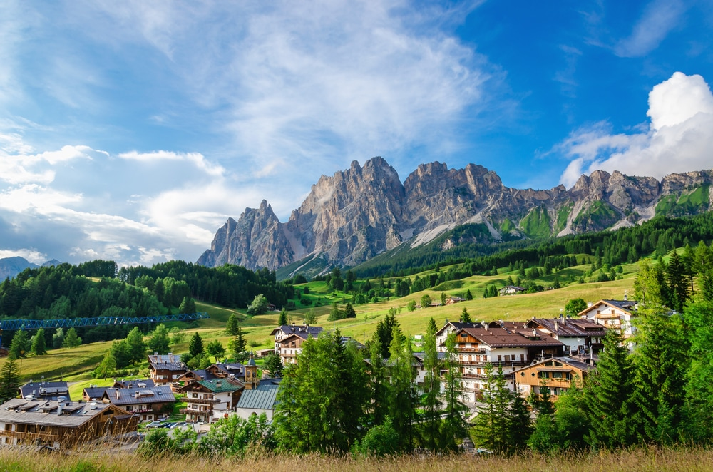 Amazing view on Cristallo Mountains with alpine village on sunny summer day, The Dolomites Mountains, Italy