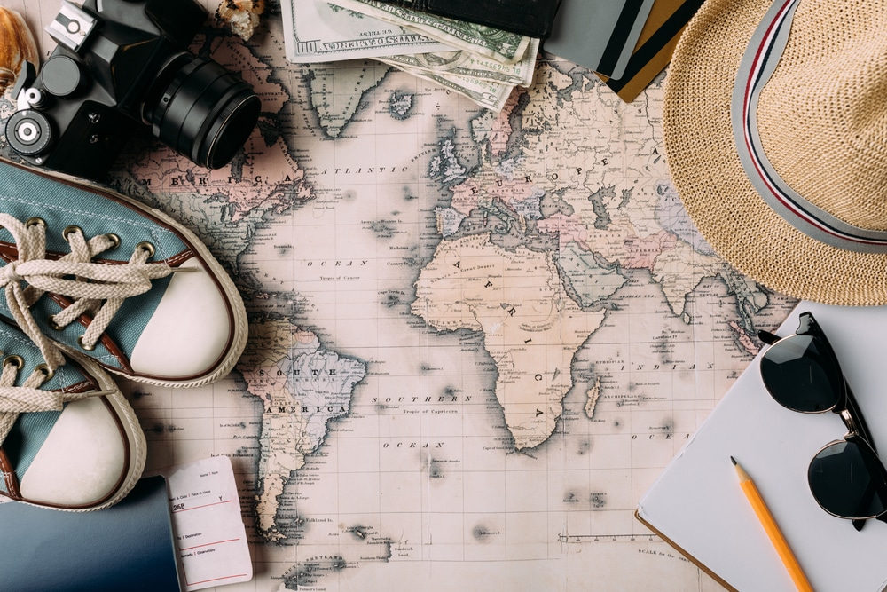 hat, passport, ticket, shoes, camera, etc. on top of a world map