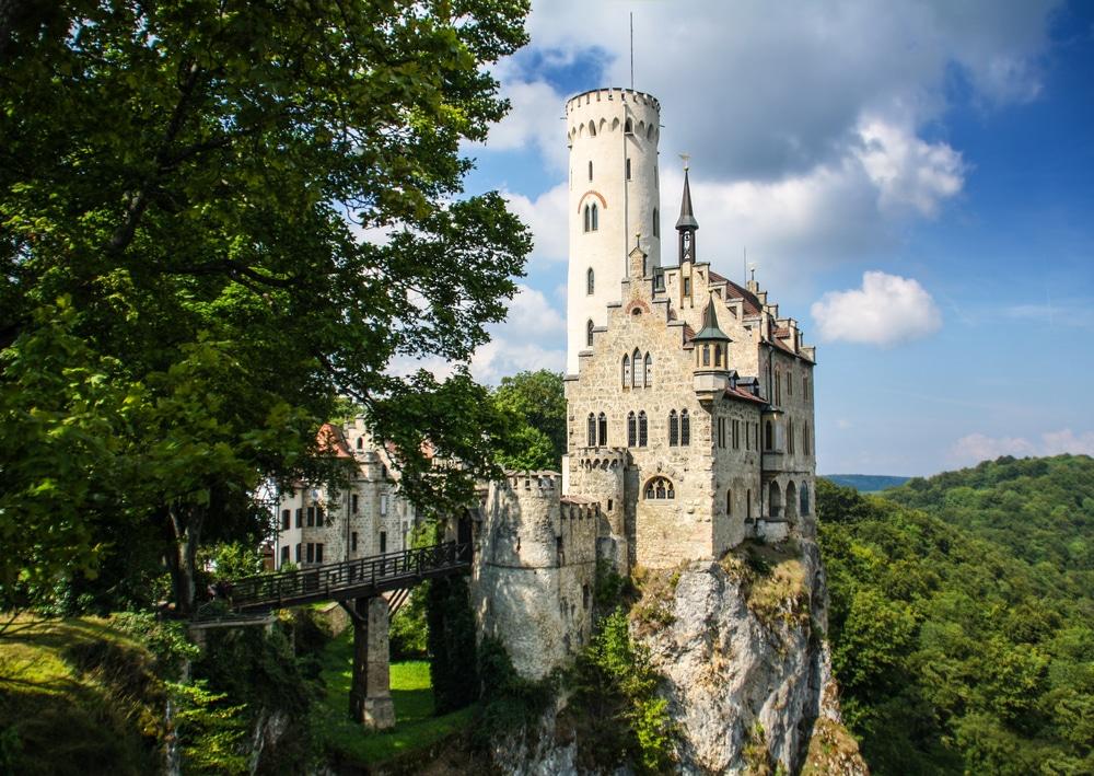 Lichtenstein castle in Germany—castle on edge of cliff overlooking forest