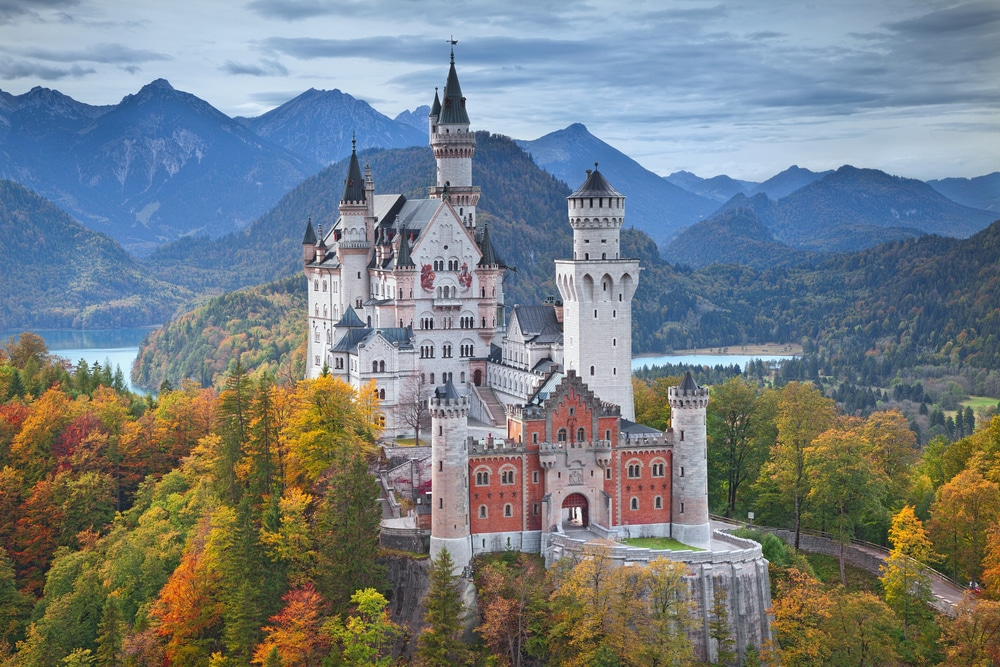 newchwanstein castle in Germany—castle on a hill surrounded by tall trees and a lake