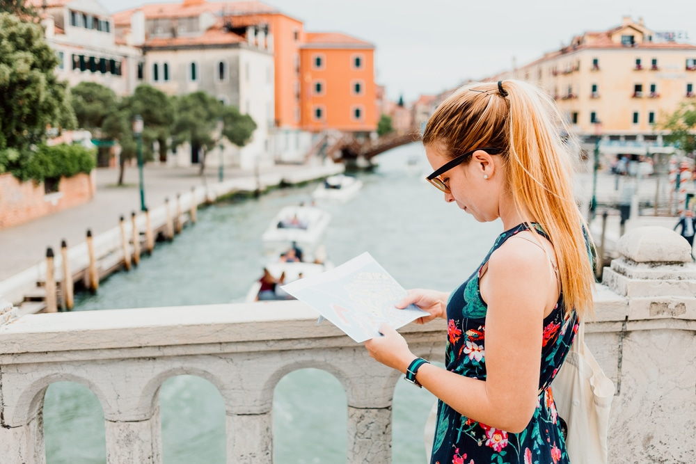 woman looking at a map on bridge in Venice