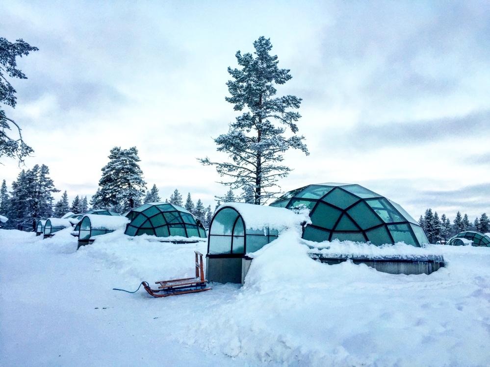 glass igloos covered in snow in Kakslauttanen resort