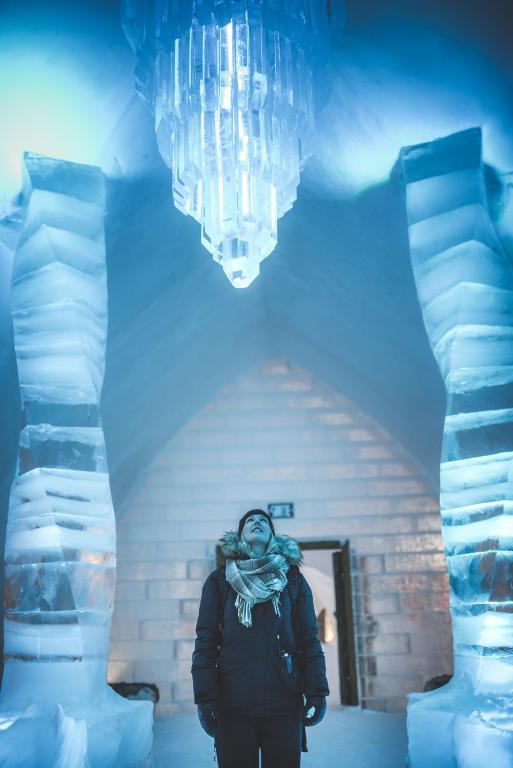 woman gazing up at ice chandelier in ice hotel