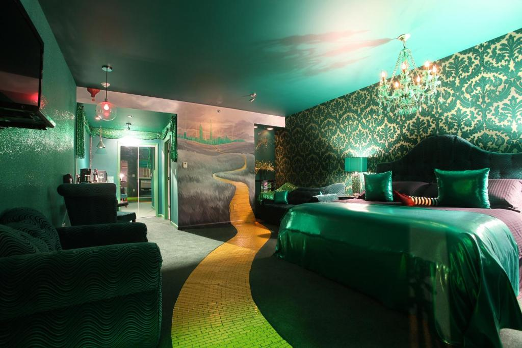 interior of Wizard of Oz room at Roxbury Hotel, very green with gold accents, wicked witch feet on bed, mural of yellow brick road on floor and wall